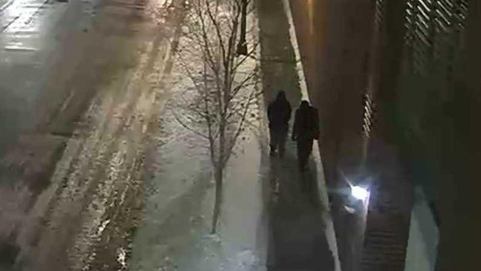 Dos personas caminando por una calle