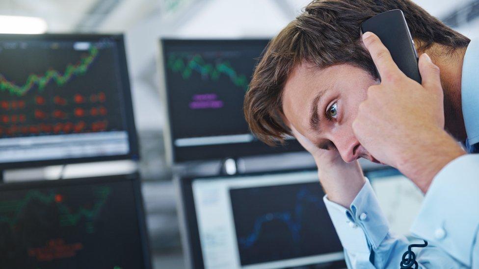 Hombre preocupado atiende el teléfono delante de pantallas de computadora.