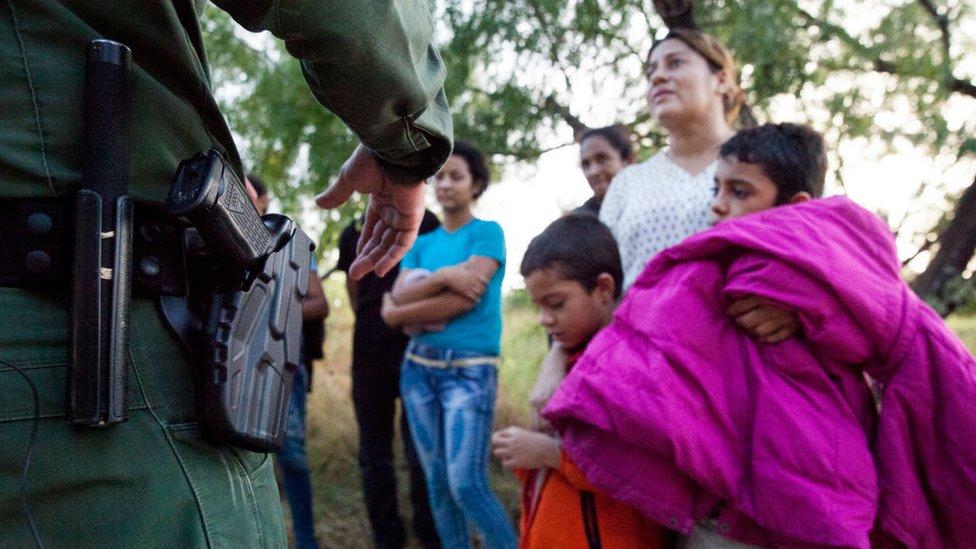 Oficial estadounidense interroga a migrantes en Texas.