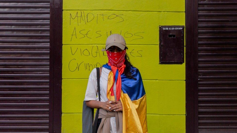 """Una manifestante con el rostro cubierto frente a un muro con un grafiti que lee: """"Malditos, asesinos, violadores, ciminales"""", en Medellín, 19 de mayo de 2021"""