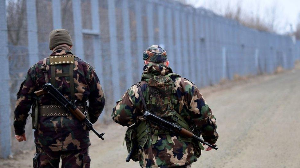 جندان مسلحان يتفقدان الحاجز الحدودي بين المجر وصربيا