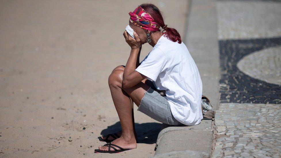 A woman covering her face sat on the pavement in Rio de Janeiro.