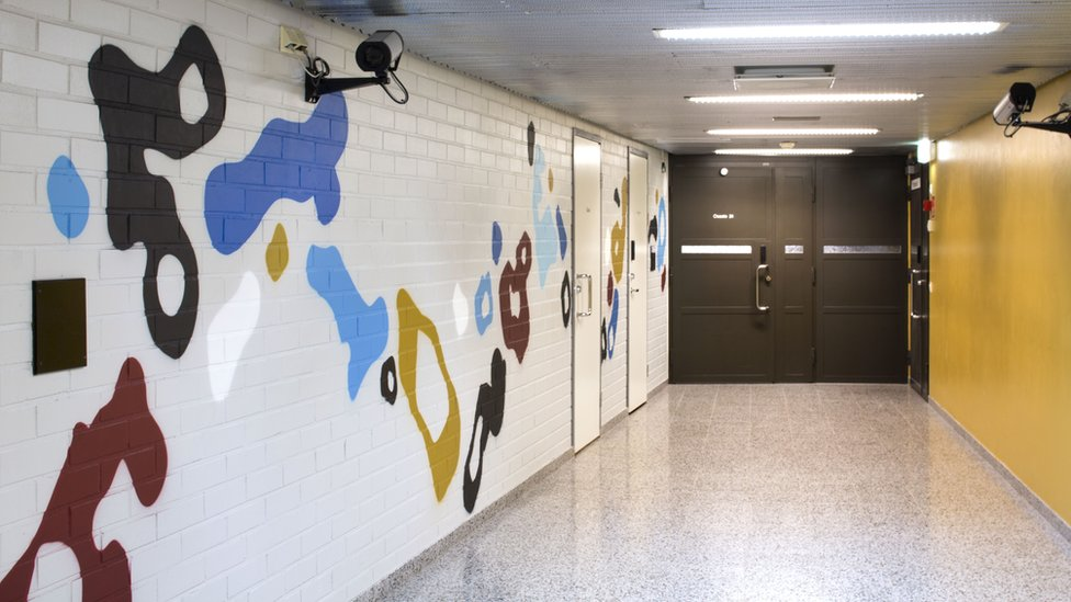 A corridor inside the prison with the EGS mural on one wall