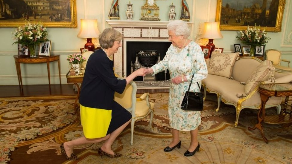 Queen Elizabeth II welcoming Theresa May (seen bowing, performing curtsy - a formal greeting made by bending the knees with one foot in front of the other) at the start of an audience in Buckingham Palace, London