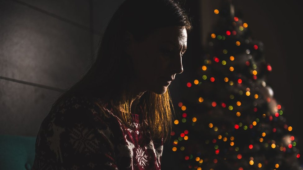 Una mujer sola al lado de un árbol de navidad