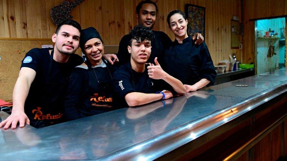 Migrantes de Venezuela, Sudán, Marruecos y Siria compartiendo la cocina del restaurante Refusión.