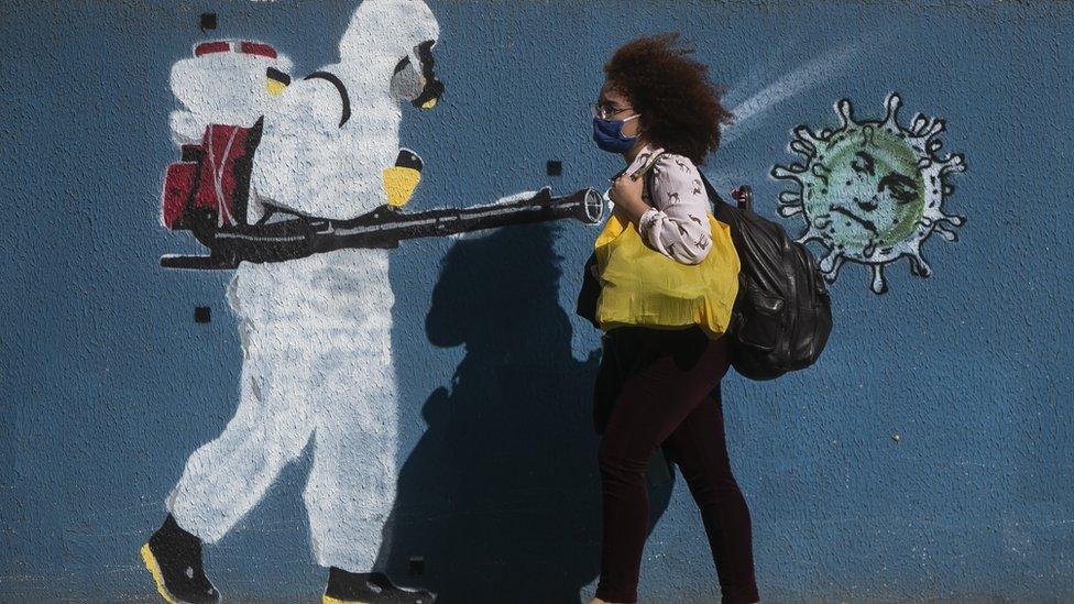 Woman walks past street mural in Brazil