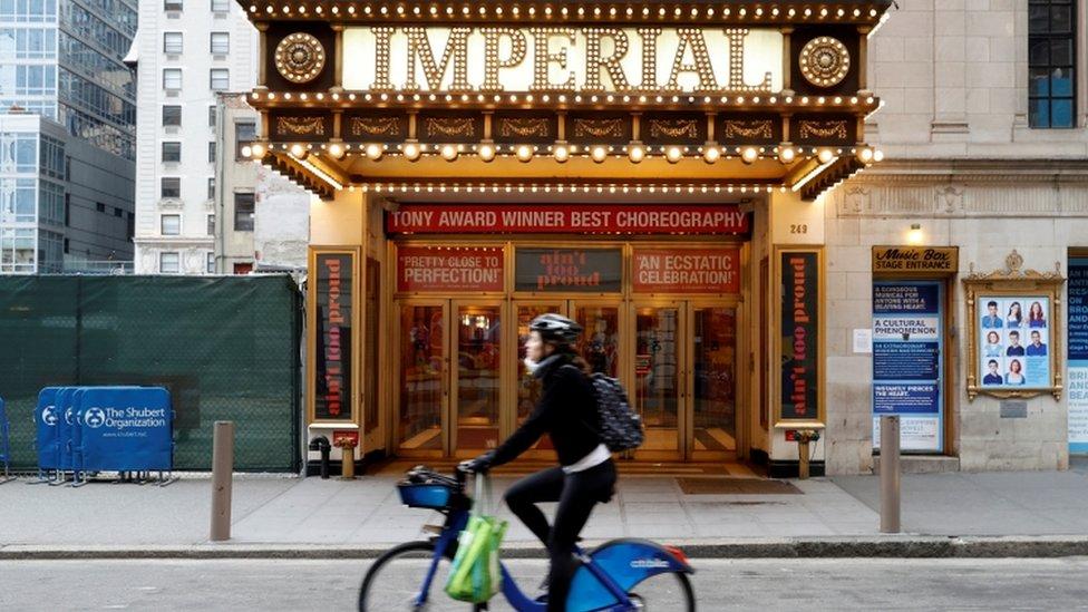 """امرأة تركب دراجة أمام مسرح """"إمبيريال"""" المغلق في تايمز سكوير. 12 مارس 2020"""