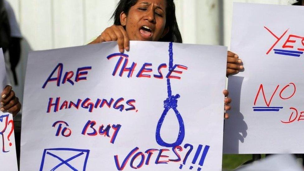 """Una mujer que protestaba frente a la prisión de Welikada el 28 de junio tiene una pancarta que dice """"¡¿Son estos ahorcamientos para comprar votos?!"""""""