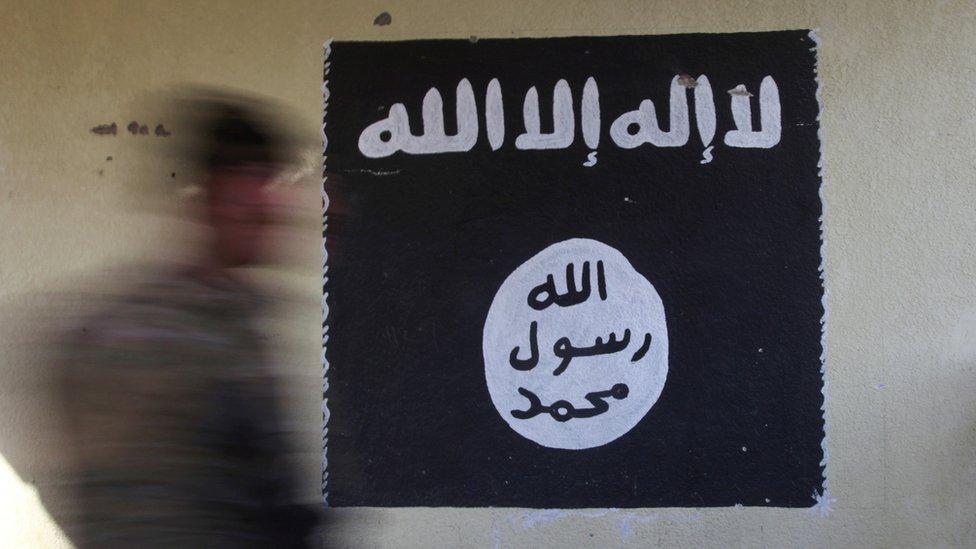 Imagen pintada en una pared de la bandera negra asociada con Estado IslámicoIraq,
