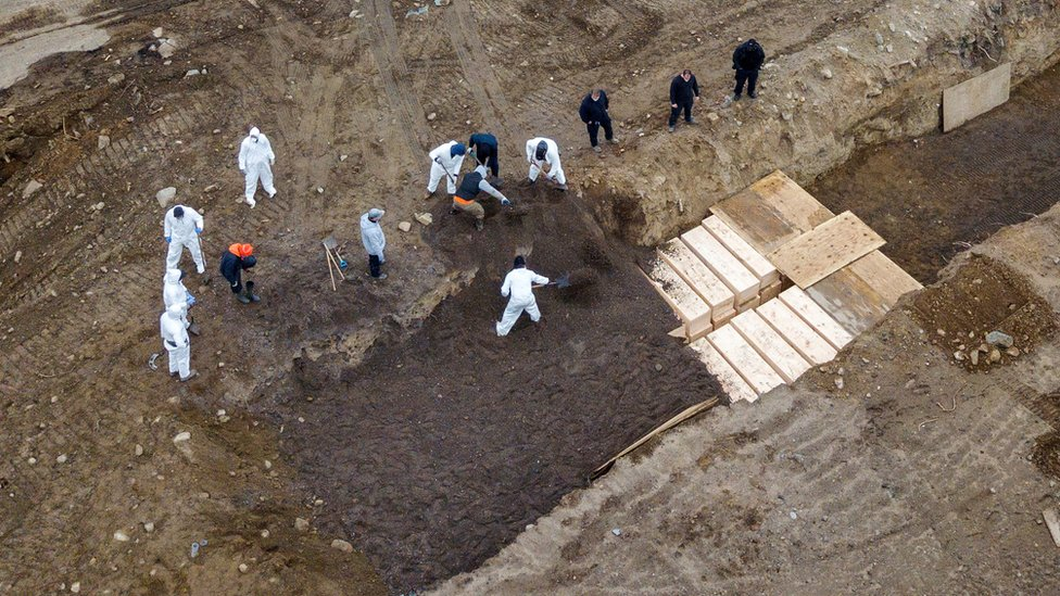 Bodies being buried in mass graves.