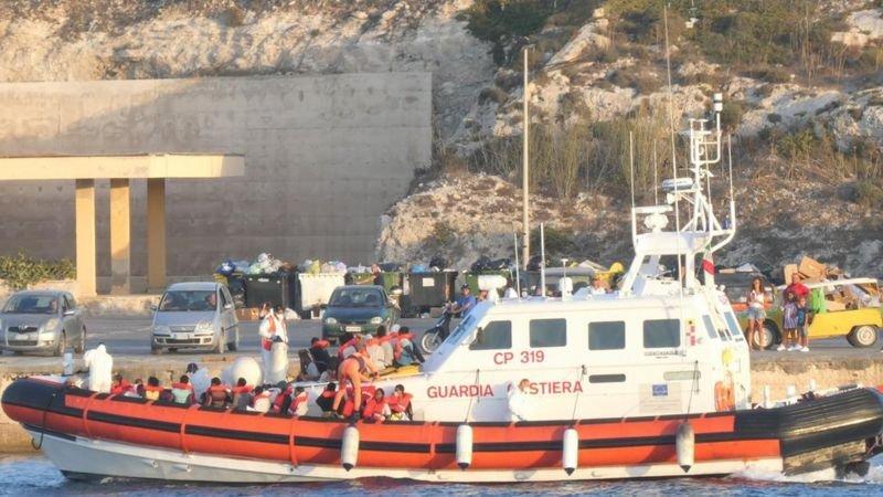 زورق دورية لخفر السواحل الإيطالي محمّل بالمهاجرين الذين تم إنقاذهم في طريقهم للنزول في ميناء لامبيدوزا، إيطاليا، 30 أغسطس/آب 2020