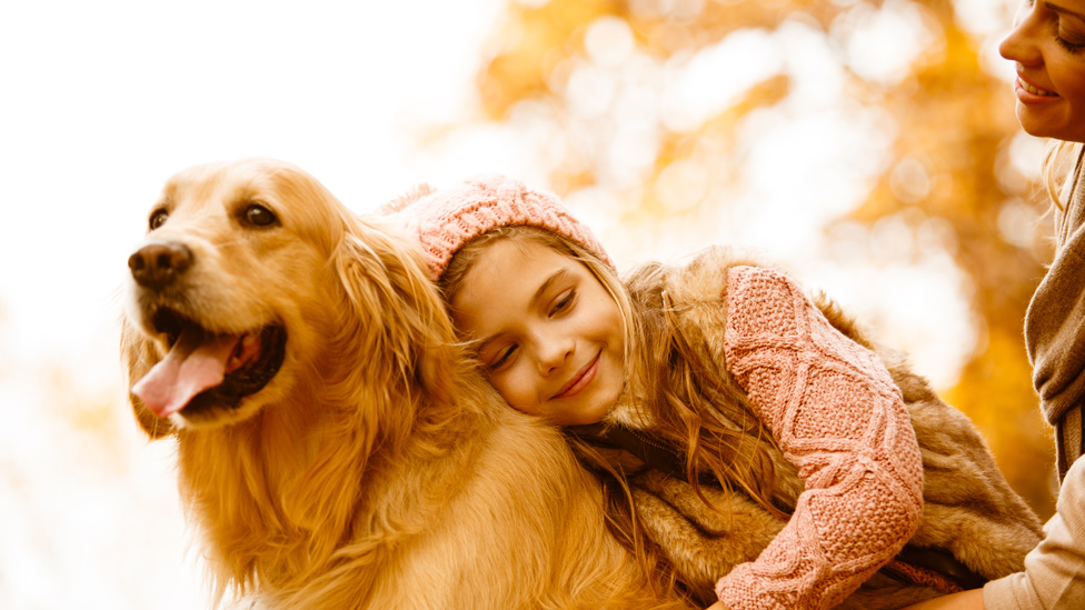 Madre y niña con un golden retriever