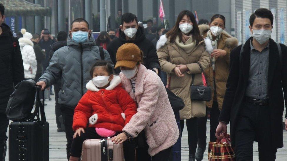 Viajeros chinos caminando con mascarilla.