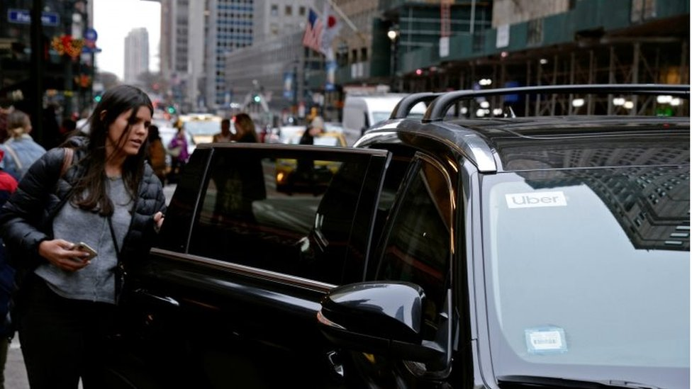 Una mujer aborda un auto del servicio Uber