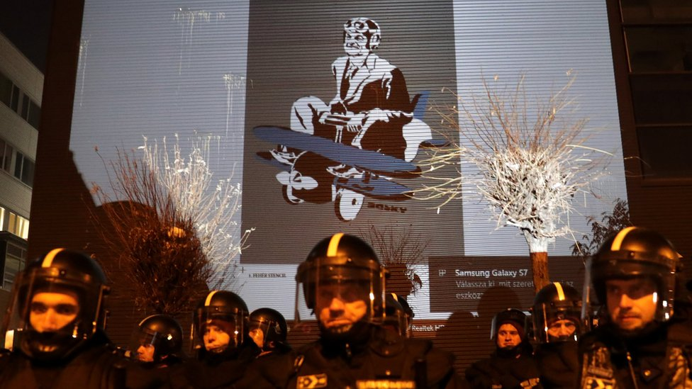 Humorous images of Viktor Orban were projected on the wall of the state TV building