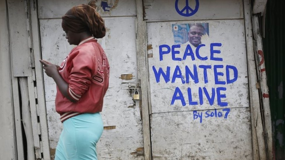 """A woman walks past a shop with a message of peace painted recently by local street artist Solomon Muyundo, also known as Solo7, on its door in Kibera slum, one of the opposition leader Raila Odinga""""s strongholds in the capital Nairobi, Kenya, 23 July 2017."""