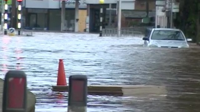 Partially submerged car in a flooded high street