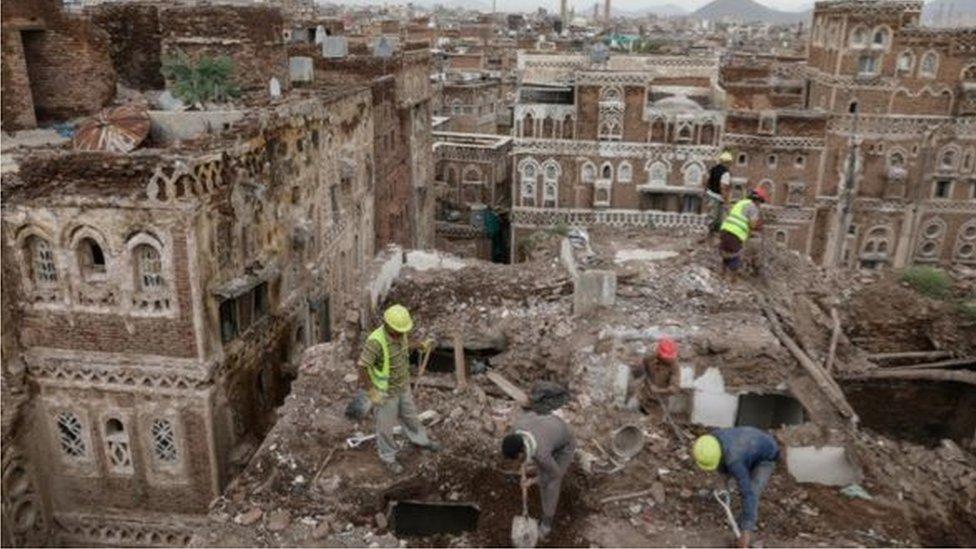 عمال يزيلون أنقاض مبنى دمرته مياه الأمطار في صنعاء