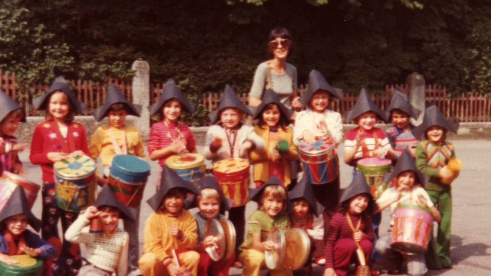 Children wearing black peaked hats kneeling in front of a teacher