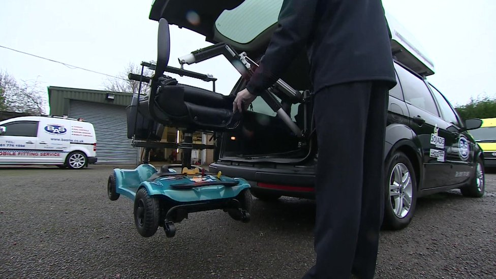 Specially-adapted Motability car lifting a wheelchair