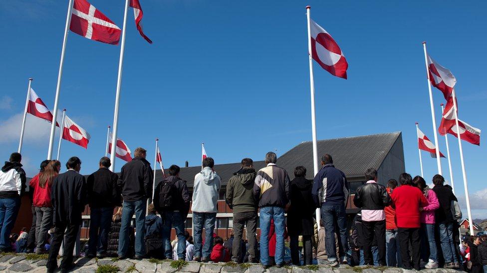أشخاص يقفون أمام علمي الدنمارك وغرينلاند