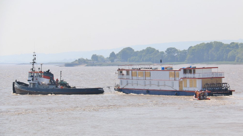 A Mississippi-style paddle steamer being towed by a lifeboat to shore after sinking