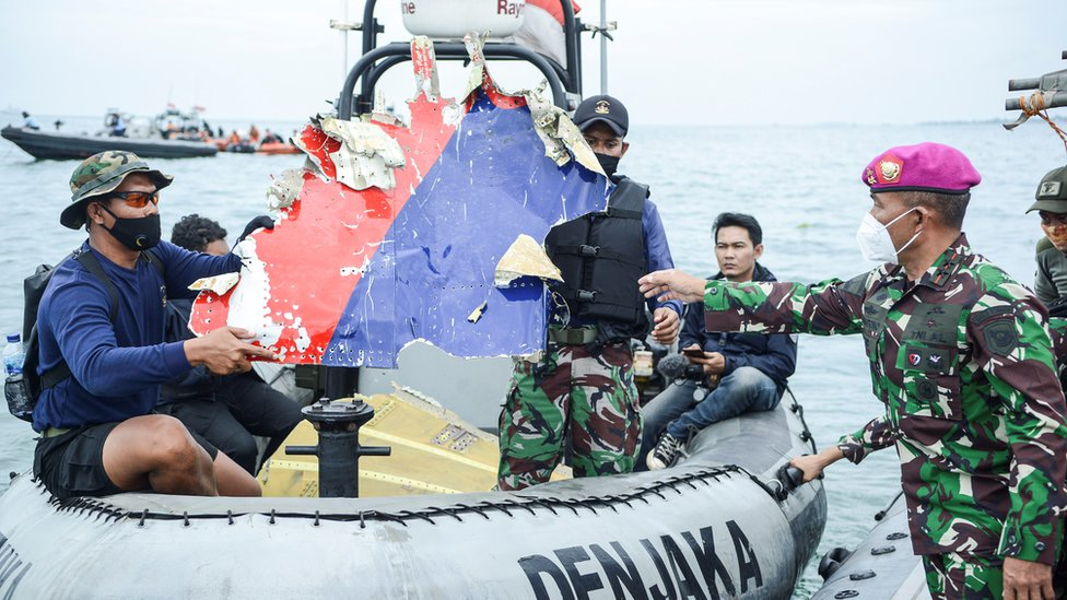 Indonesian Navy personnel carry debris believed to be from the Sriwijaya Air SJ-182 plane,