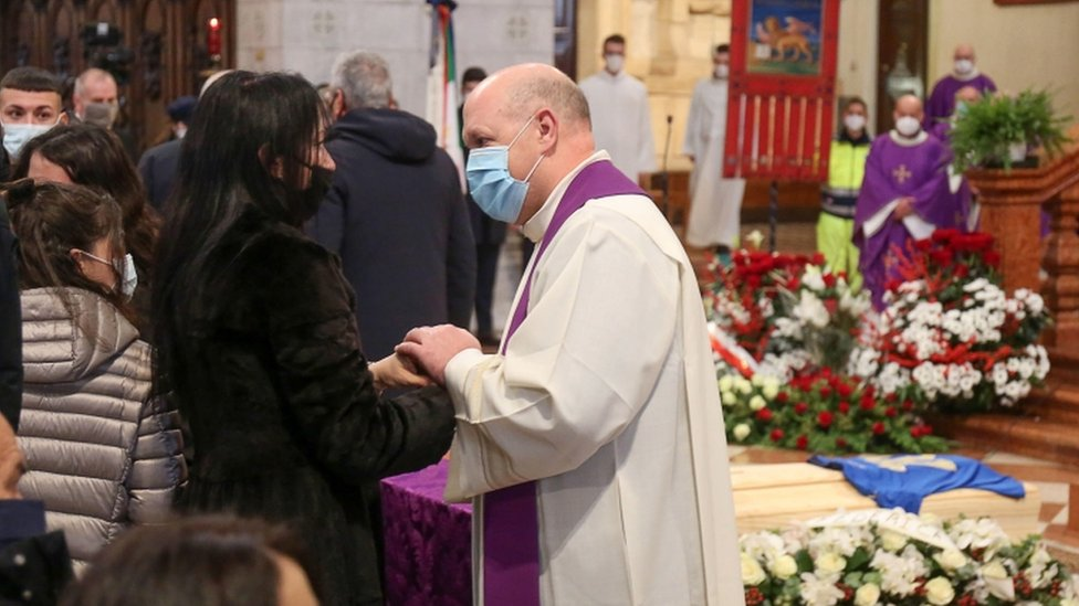 A priest comforts Rossi's widow Federica Cappelletti in front of the coffin