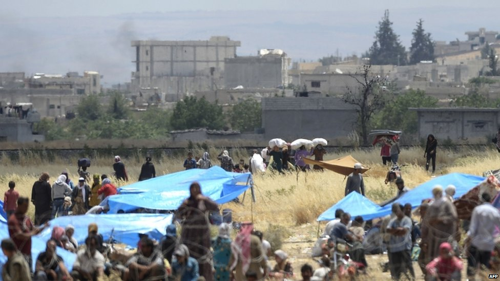 Civilians head towards the Syrian town of Kobane from Turkish territory, 27 June