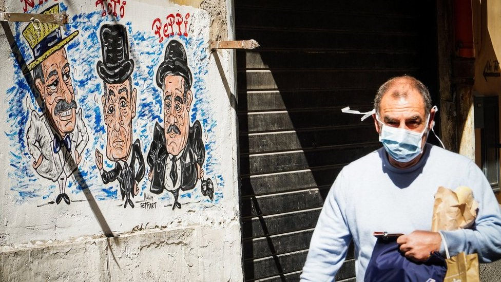 A person wearing a protective face mask walks at Quartieri Spagnoli, Naples, Italy, 18 March 2020