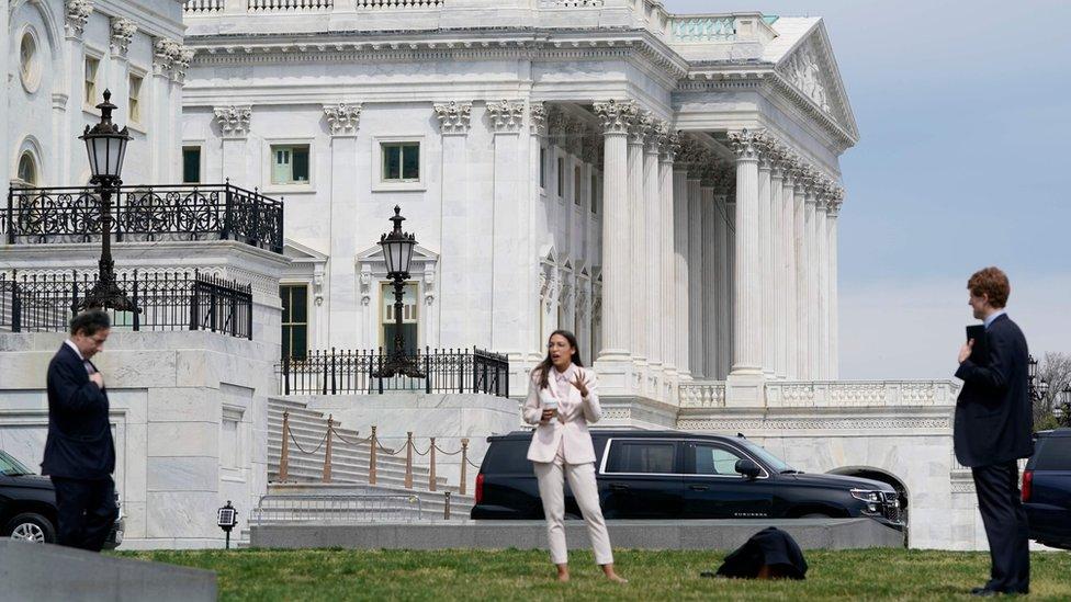 أشخاص يقفون أمام مبنى الكونغرس الأمريكي