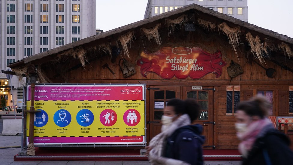 People wearing face masks walk past the stands of the Potsdamer Platz Christmas Market
