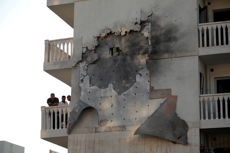 People look out from an apartment building which was damaged by a rocket fired from Syria, in Nusaybin, Turkey, 10 October 2019.
