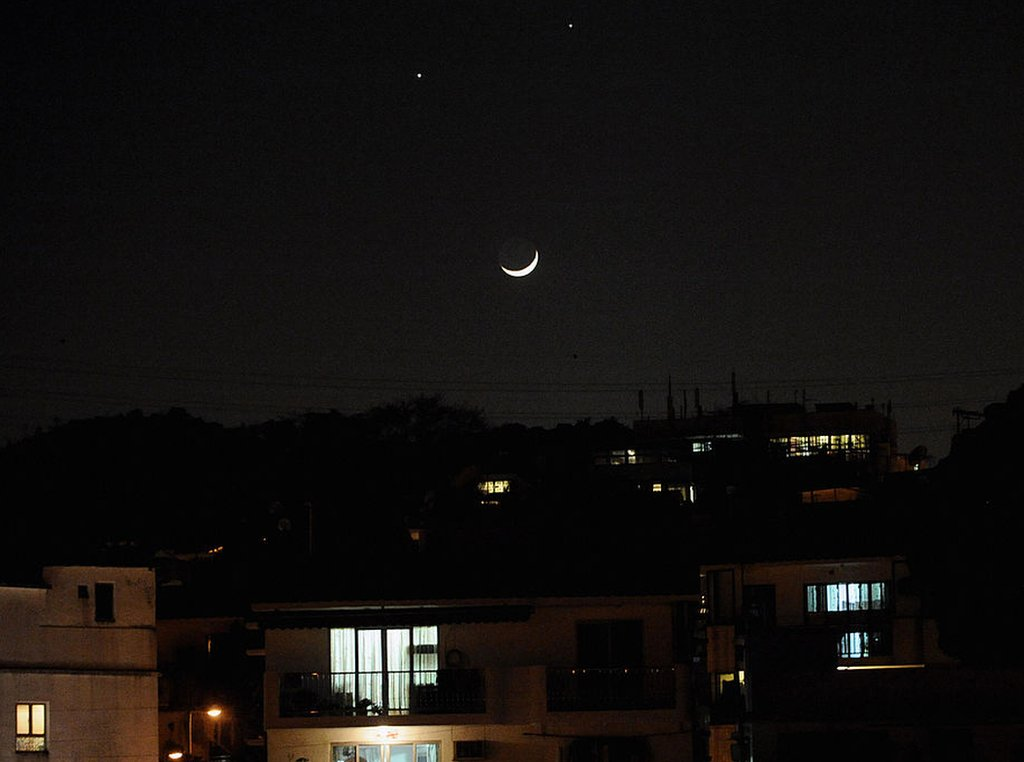 A crescent moon (below) and the planets Venus (left) and Jupiter (right) are seen in a rare alignment over Hong Kong on December 1, 2008