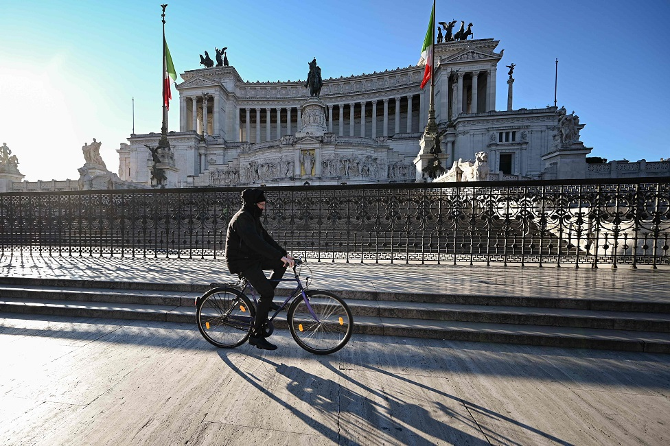 A man cycles past a monument in Rome