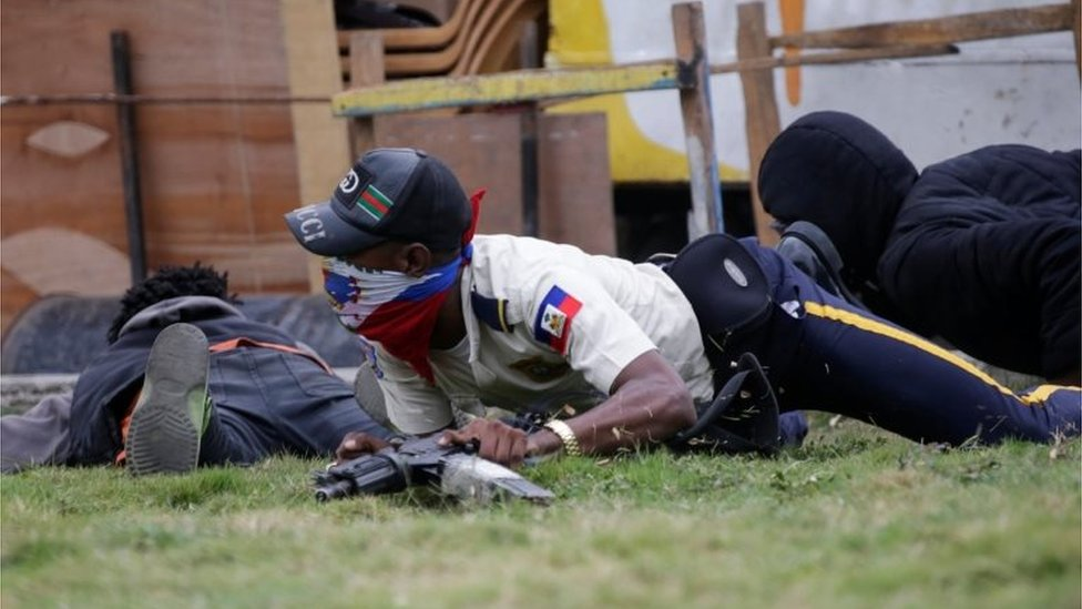 A masked man in a Haitian National Police uniform crawls on the ground during a shooting in Champ de Mars, Port-au-Prince, Haiti February 23, 2020