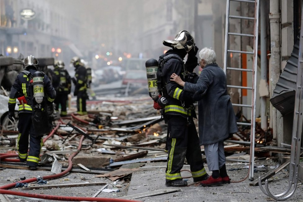 An elderly woman evacuated from a damaged building holds the arm of a fiefighter