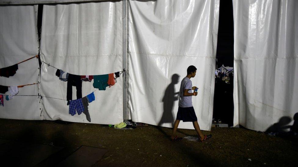 Joven de la caravana de migrantes caminando cerca a unas prendas colgadas.