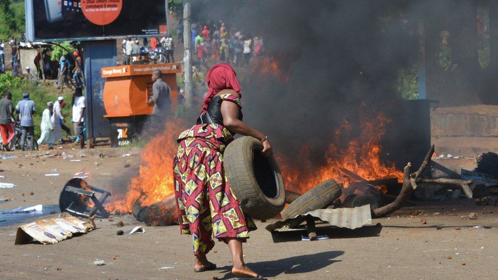 A protester burns tyres during the funeral after the last street protests and unrest that resulted in nine deaths in Conakry, on November 4, 2019. - Crowds of protesters marched through the Guinean capital of Conakry on October 24, 2019 in the latest round of demonstrations against President Alpha Conde, accused of trying to circumvent a bar on a third term in office