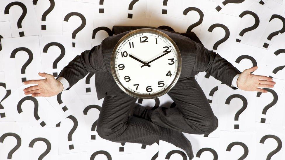 Un hombre rodeado de signos de pregunta con un reloj en la cabeza.