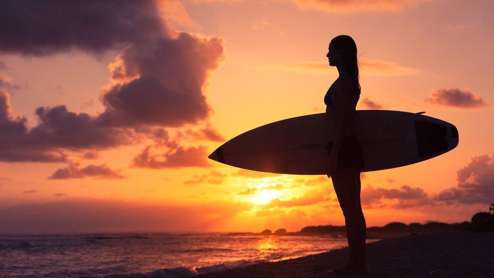 Mujer con una tabla de surf en un atardecer.
