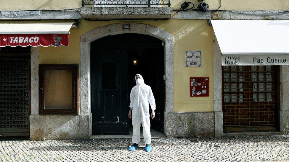 Homem com traje de proteção em rua de Lisboa
