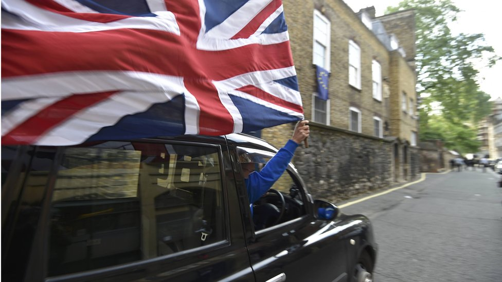 A London taxi driver waves a union jack flag from his cab.