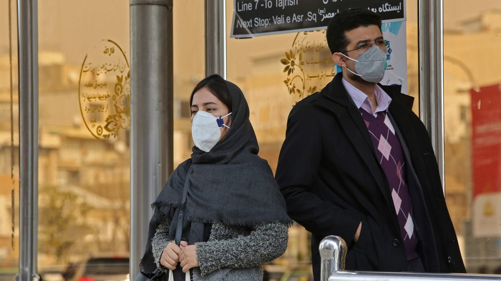 People wearing protective masks stand at a bus station in the Iranian capital Tehran on February 24, 2020