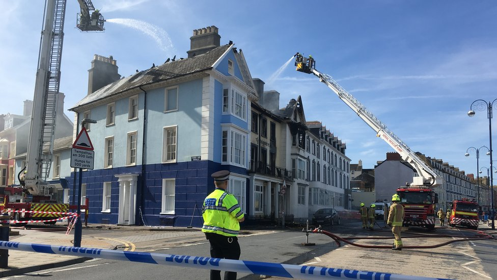 Cranes spray the building with water behind a police cordon