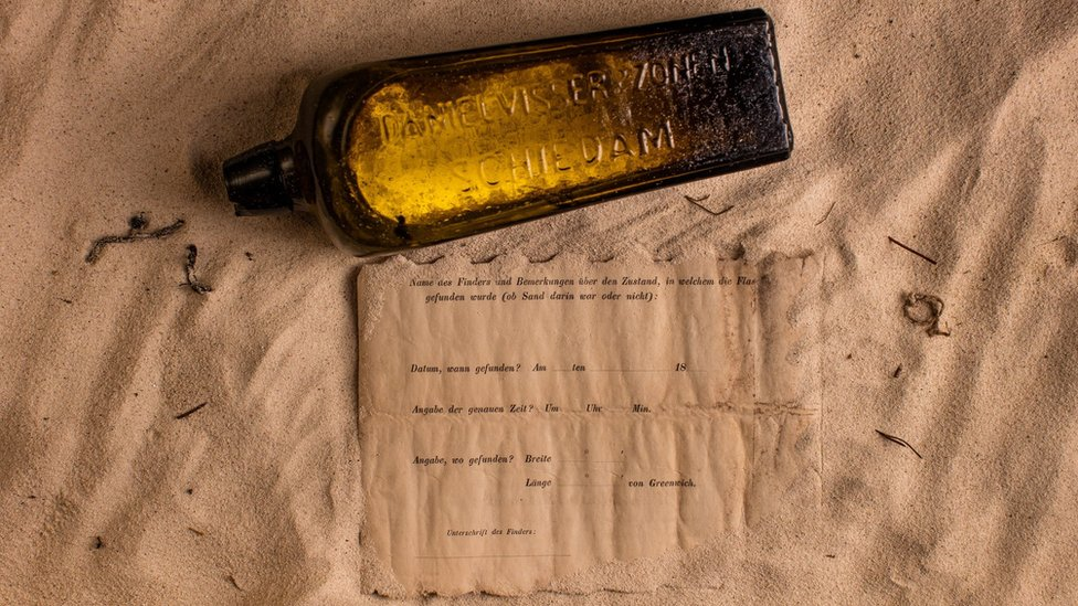 The bottle and the note placed on a sandy surface