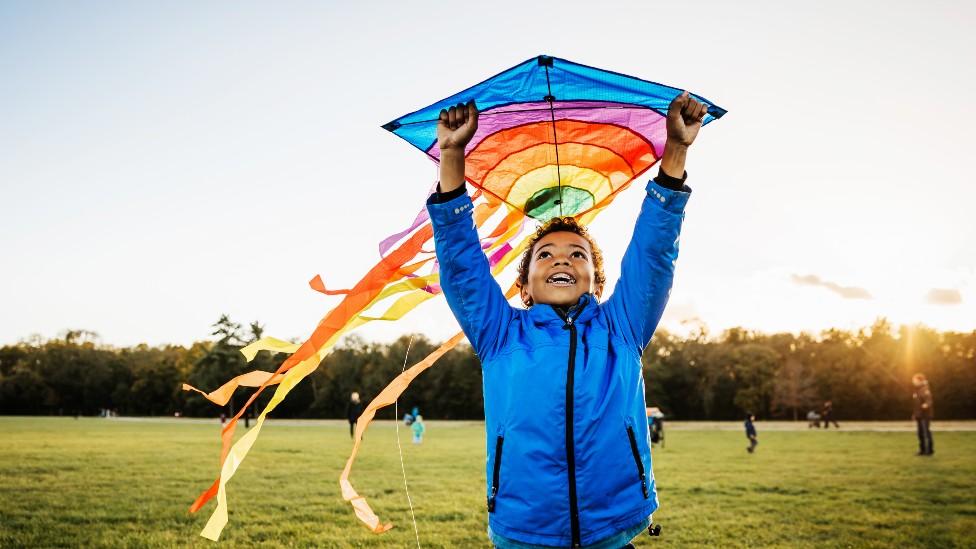 Un niño jugando con un cometa en un parque