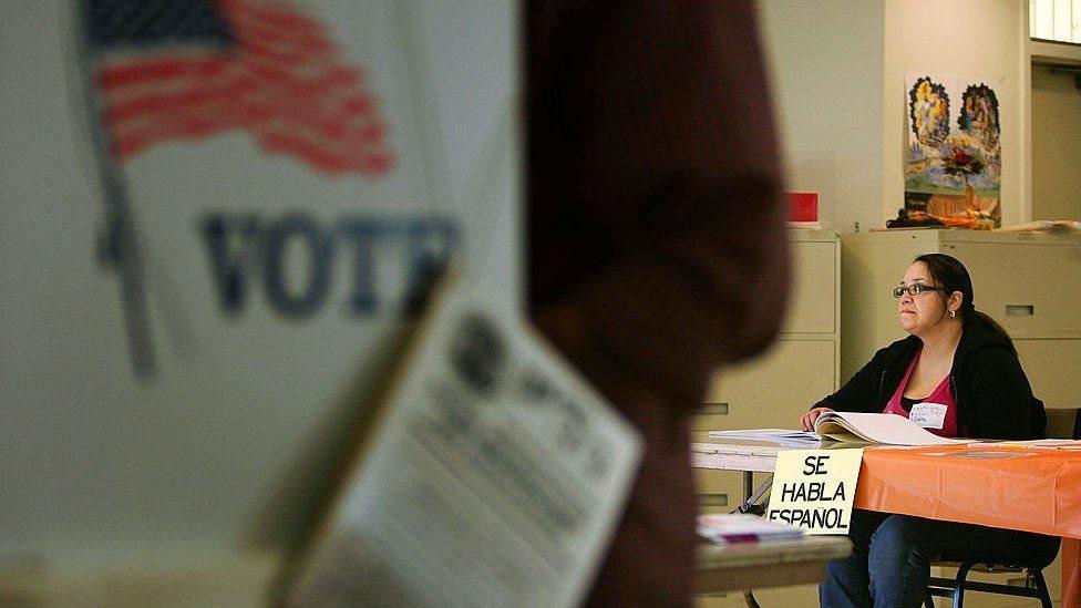 """Un centro de votación en Estados Unidos en el que una mujer está sentada en una mesa de la que cuelga un aviso que dice """"Se habla español""""."""
