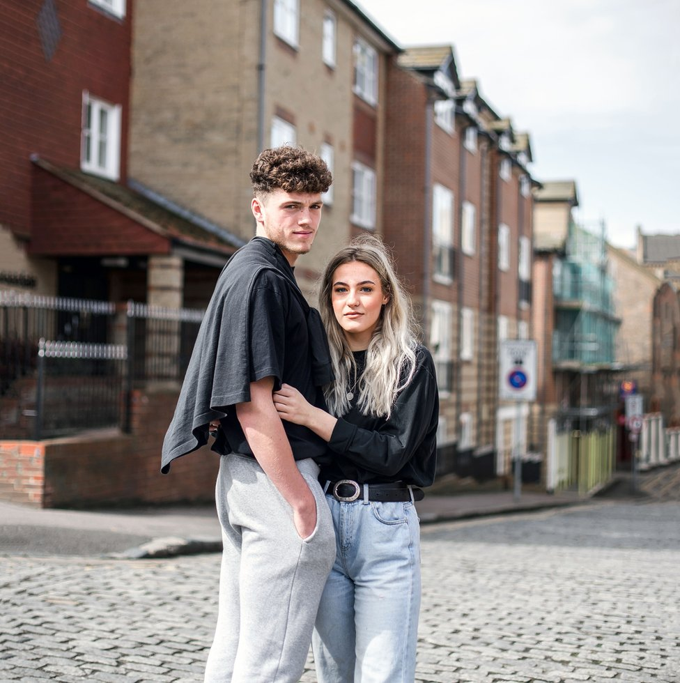 Portrait of a young couple standing in a street